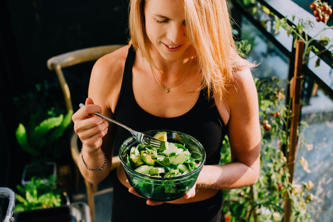 Clean eating. Women eating a green salad with avocado.